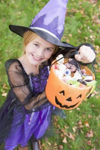 Girl dressed as a Witch in purple with a jack-o-lantern full of Halloween Candy