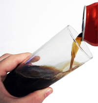 pouring cola from a red can into a glass