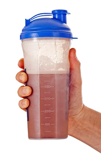 man's hand holding a Protein Shake in a plastic Container