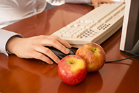 hand next to apples and a computer keyboard