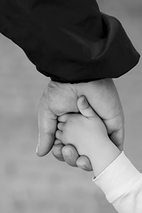 balck and white photo of adult hand holding child's hand