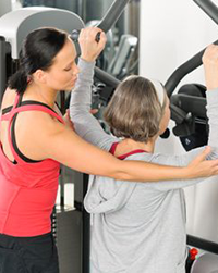 woman trainer helping woman on excercise machine