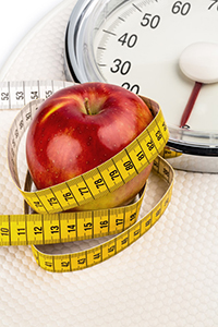 Apple wrapped in a measuring Tape on a Scale