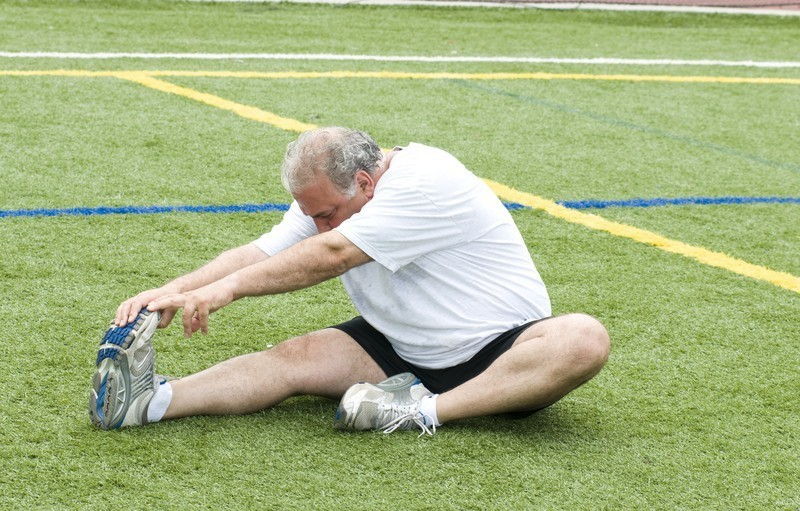 man sitting on a field stretching his right leg