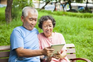 Happy Seniors Couple With Tablet Pc In The Park