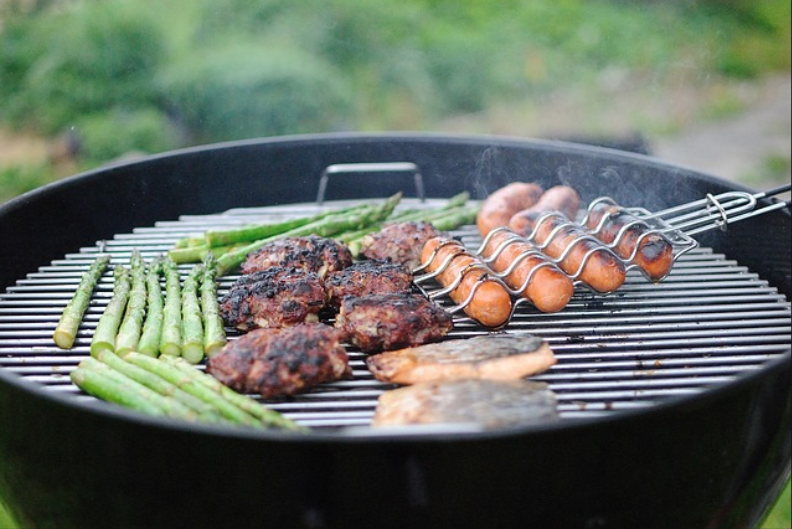 Veggies and meat on a grill with tongs